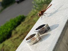 Zilveren ringen gemaakt uit Wilhemina guldens, met een libelle op de achtergrond..