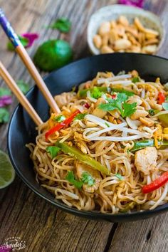 Chicken Pad Thai rice noodles with red bell peppers, carrots and peanuts in a large black bowl on a wooden table.