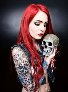 Sleeve tattoo of skulls and pentagram. Redhead holding a skull.