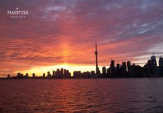 The Toronto city silhouette against a vibrant sunset.