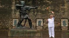 Torchbearer Barbara Green poses with the Robin Hood statue before she carries the Olympic Flame on the Torch Relay through Nottingham. Olympic Flame, Nbc Olympics, Near To You, Nottingham, Opening Ceremony, Derby, Poses, Statue, London