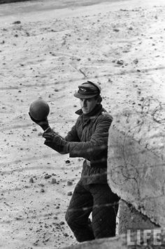 East German border guard tossing a ball back over the Berlin Wall after a West German child mistakenly threw it over, Berlin, Germany, by Paul Schutzer, 1962