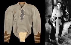 "Tom Tyler hero ""Capt. Marvel"" tunic from Adventures of Captain Marvel: ""This pale grey wool tunic features asymmetrical false front closure with lightning bolt insignia and gold bullion gauntlets. Worn by Tom Tyler while battling the evil Scorpion in this classic 1941 serial."""