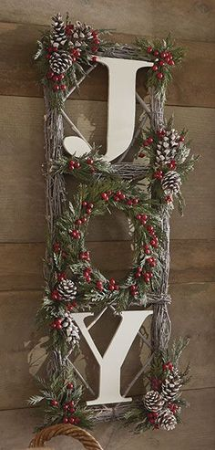"""Designed with natural twigs, green preserved cedar, snowy pinecones and faux red berries. A favorite holiday sentiment in white wooden letters. For indoor or outdoor (in protected area) use. 31""""H x 12""""W x 3""""D. Avoid direct sunlight, heat or moisture."""
