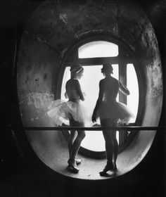 Ballerinas standing between barre and round windows against which they are silhouetted during rehearsal for Swan Lake at Grand Opera de Paris  byAlfred Eisenstaedt
