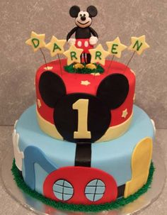 Torta en 2 pisos en doble altura cubiertas en fondant azul y rojo con decoraciones a contraste y parte superior con la figura de Mickey y el nombre del niño para celebrar 1 año
