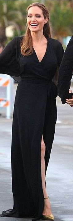 Who made  Angelina Jolies gold strap ankle pumps and black wrap maxi dress that she wore in Santa Monica on March 1, 2014?
