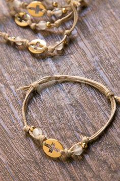 Μαρτυρικά βάπτισης βραχιόλι από κερωμένο μπεζ κορδόνι με χρυσαφί μεταλλικό σταυρό, διάφανες και χρυσές χάντρες