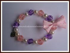"""Pulsera de perlas y daditos acrílicos en colores rosa y lila transparente, lleva una lacito rosa de grosgrain y un charm en plata """"made with love"""""""
