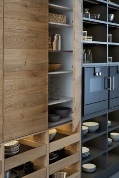 Warm wood and black matt shelving and cupboards make for a striking kitchen modern style.