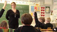 Opettaja seisoo luokan edessä ja lapset viittaavat.