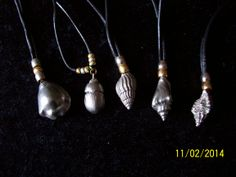 Solid pewter pendants on leather and gilded fittings.