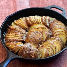 Brush bottom, sides of a baking dish/cast iron skillet with olive oil. Using a mandoline or sharp knife, slice potatoes crosswise into desired thickness. Arrange slices vertically, loosely in prepared dish/skillet. Sprinkle garlic, Italian seasoning on top. Season with salt, pepper to taste. Dot with butter. Cover with foil, bake at 375 F in oven about 1 hour or until tender. Remove foil, sprinkle parmesan, bake another 15-20 min until crisp. Sherry Brown, Cast Iron Cooking