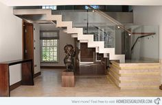 A free standing staircase made with cement flooring and LED backlights, completed with glass railings