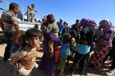 Syrian Kurdish wait for transport as thousands of new Syrian refugees from Kobani arrive at the Turkey-Syria border crossing of Yumurtalik near Suruc, Turkey, Wednesday, Oct. 1, 2014. U.S.-led coalition airstrikes targeted Islamic State fighters pressing their offensive against a Kurdish town near the Syrian-Turkish border on Tuesday in an attempt to halt the militants' advance, activists said. (AP Photo/Burhan Ozbilici)