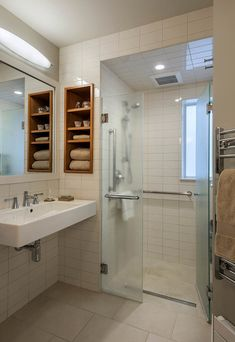 """Level in, zero threshold shower, open clearance sink - bath in """"writer's retiement abode"""" suggests future planning for possible accessiblity needs - but not truly wheelchair user accessible (towels, out of reach range, mirror set too high to look in if seated) - still a start at UD"""