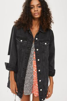 This season is all about longline denim jackets. In washed black cotton with a distressed hem, this directional denim cover-up features four pockets, buttons through the front, and rips in the elbow for that rebellious lived-in look.