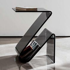 Intricately curved glass coffee table available in smoked or extra clear glass. This glass table is formed in such a way that the glass element provide quirky storage. the proportions of this design make it a great curved glass side table