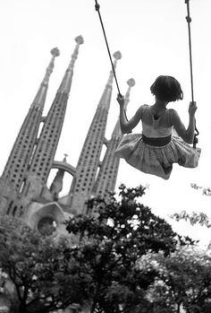 the sagrada familia (young girl on swing in playground with the towers of the gaudi cathedral in the background), barcelona, 1959    photo by burt glinn/magnum photos