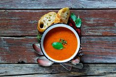 #Tomato soup Gazpacho  Tomato soup Gazpacho in vintage metal bowl with fresh baguette chili garlic and basill on rustic wooden background top view copy space.