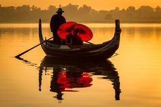 A boat ferries monks with parasols across Taungthaman Lake, near Amarapura in Myanmar, at sunrise casting a reflection on the still water of the lake.