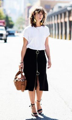 A white t-shirt is paired with a knee-length skirt, ankle-strap heels, a Loewe Puzzle Bag, and statement earrings