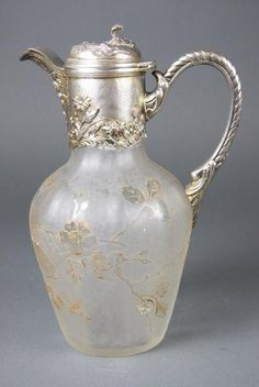 A French Art Nouveau silver plate-mounted cameo glass Claret Jug, late 19th century, unmarked but possibly Daum of ovoid ewer form, The colorless frosted body decorated with parcel-gilt flowering and fruiting branches, mounted with a single piece silver-plate collar, handle and spout with hinged cover, all cast with fruiting and floral plants