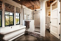 LOVE this bathroom - subway tile shower with wood ceiling and black accents