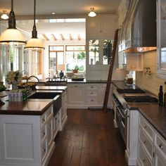 Giannetti Home: Beautiful U shaped kitchen with white inset kitchen cabinets paired with black perimeter ...
