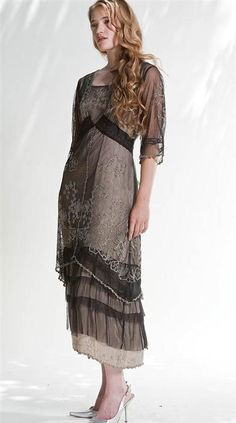 Taupe under-lining with sheer black overlay and is embroidered with inset lace and bias-cut flounces.