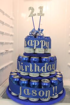"This is how I do birthdays...  I found a cake like this on pinterest previously but there were no directions...  Here's how I did it:  3 of each 8"", 12"" and 16"" cake boards. I painted mine blue.  Hot glued them together. Use an empty can to trace placement of cans on each cake board. This takes 53 cans of beer...yes...53 cans...wired ribbon to wrap the cans after taping them all down. Adhesive letters to embellish the ribbon. Homemade cake topper with glitter, dowels and curly ribbon."