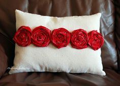 Canvas pillow embellished with pretty red fabric rosettes