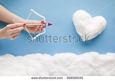Two hands shooting an arrow to a cotton-wool heart, in a heavenly scenery with cotton wool clouds on a blue sky paper background.