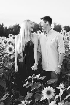 Simply Picturesque Maryland Lifestyle Photographer couple in sunflower field looking at each other holding hands smiling at each other black and white photography