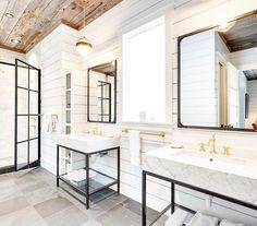 Modern Farmhouse bathroom has wood plank ceiling, large square tile floors and two vanities instead of one double.