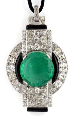 DIAMOND BROOCH/PENDANT, of Modernist design, centring on a circular-cut emerald weighing 13.64 carats, within an annular surround of circular-cut diamonds accented with black lacquer, cut-through with a similarly-set stepped rectangular section, suspended from its original silk cord, later restored brooch fitting, 1924-1930. Accompanied by a photograph courtesy of the Fouquet Archives conserved by the Musée des Arts décoratifs, Paris.