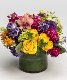 Vivid Dreams A summer favorite, this vivid collection of bright summer yellows, fuchsias, and purples - including roses, lisianthus, and orchids - is gathered as a low and lush design in our leaf-lined cylinder vase.