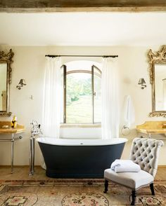A freestanding black tub in a feminine and traditional bathroom