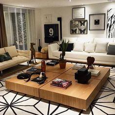 Living com dimensões favoráveis favorece a utilização de peças maiores. Nesse caso quatro mesas de centro quadradas juntas. Adorei o tapete com detalhes geométricos.