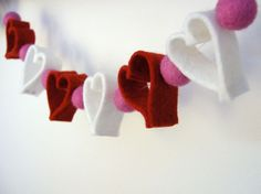 BEAUTIFUL VALENTINES DAY DECOR -- DIY Felt Heart Garland -- another blog showed same Garland using different types of pompoms in between (the tinsel type) & pompoms that were hand felted.  You could also add in bunches of fabric strips, bunting triangles, burlap pompoms, ect.  {Included are instructions for Cascading PAPER Heart Garland for kids & Cascading Felt Heart Ornament / Decoration}.  Makezine.com by Betz White