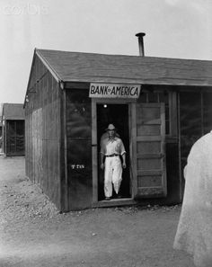 A Japanese man walks out of the Bank of America in theTule Lake Internment Camp, Newell, California, May 1943.