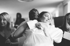 Bridesmaid hugs the bride before the wedding at the Franklin Institute in Philadelphia. Captured by NYC wedding photographer Ben Lau.