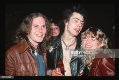 Sex Pistols singer Sid Vicious poses with two fans.