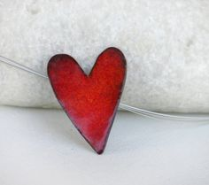 A copper heart enameled with red tint, hanging from steel wires 40cm with copper clasp. You can chooce if you want it with leather cord or gold color