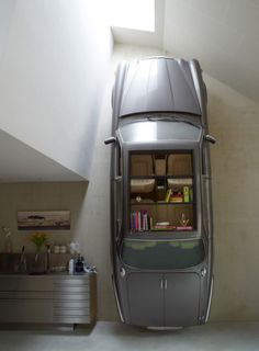 Dutch design studio Denieuwegeneratie thought to convert a car into a tall bookshelf for the interior of their newly-built Dutch Mountain underground villa. By removing its engine, cutting out a large rectangular window in the roof, and placing the vintage Jaguar upright, the once active vehicle is transformed into an intriguingly attractive storage unit and shelving space. The trunk even serves as a lower cabinet.