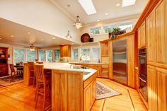 Rich wooden kitchen with curved corner containing large stainless steel refrigerator. Angled island divides the kitchen from the living area. Plenty of natural light from elevated windows above the cabinetry