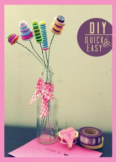 //button flower DIY quick and easy - stack of pretty buttons on some threads of wire, whacked into a glass bottle!