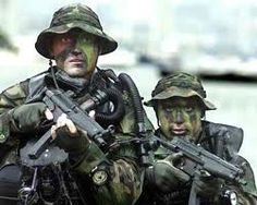 Navy SEALs emerge from the water equipped with rebreathers & HK MP-5 submachine guns.