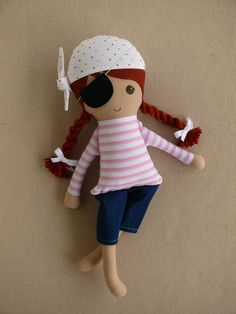 This is a handmade cloth doll measuring 20 inches. She is wearing a playful pink and white striped pirate outfit with a white and polka dotted tie-hat, dark denim cut-offs and bare feet. She has a black, felt eyepatch that is removable. Her dark red hair is worn in low, twisted braids and accented with white grosgrain ribbon bows. She is made from 100% cotton fabrics, wool blend felt, and polyester fiberfill. Her seams are triple stitched, and she is firmly stuffed.      Please hand wash…