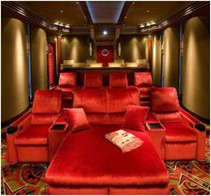 elegant home office theater room with red velvet armchairs and sofa